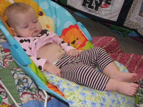 Looking like a giant girl, asleep in the almost-too-small bouncy chair